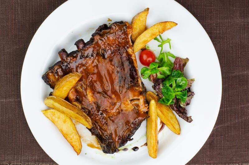 Costole di carne di maiale con la salsa del BBQ immagini stock