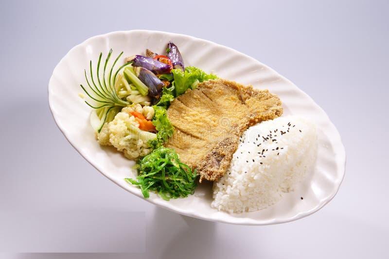Costole di carne di maiale croccanti del riso con la verdura, brocooli sul piatto bianco dentro immagine stock