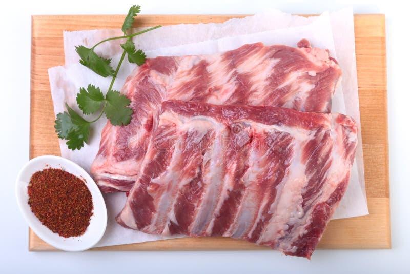 Costole di carne di maiale crude con le erbe e le spezie sul bordo di legno Aspetti per cucinare fotografia stock libera da diritti
