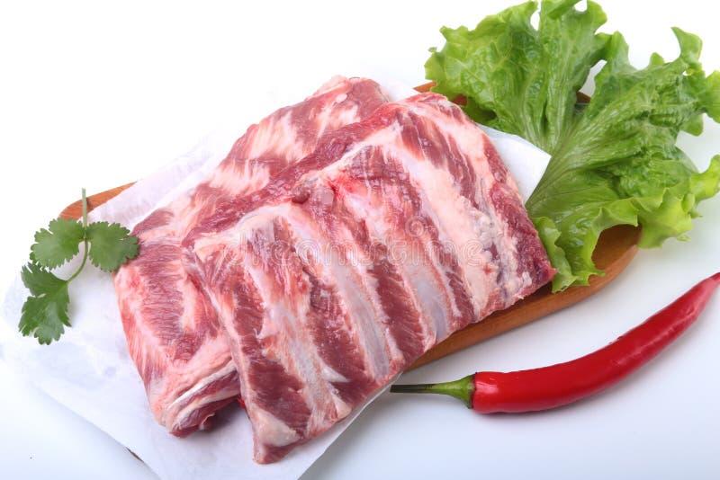 Costole di carne di maiale crude con le erbe e le spezie sul bordo di legno Aspetti per cucinare immagini stock