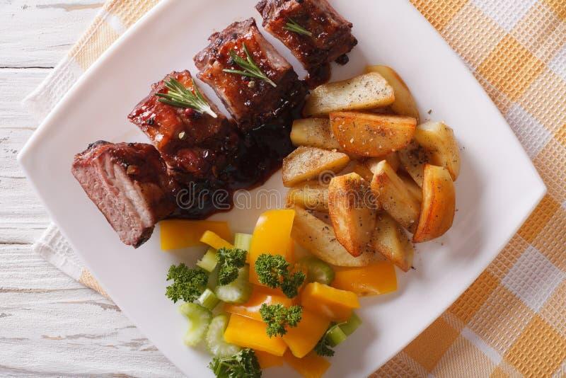 Costole di carne di maiale del BBQ con il primo piano della patata su un piatto principale orizzontale vi fotografia stock libera da diritti
