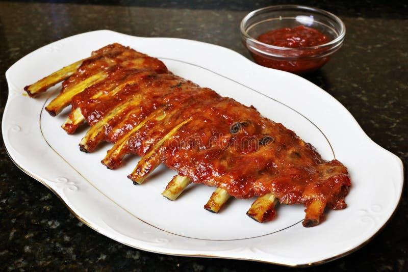 Costole di carne di maiale al forno con il barbecue o la salsa del BBQ fotografie stock
