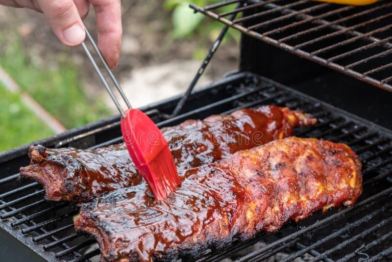Costole di carne di maiale che cucinano sulla griglia del barbecue immagine stock
