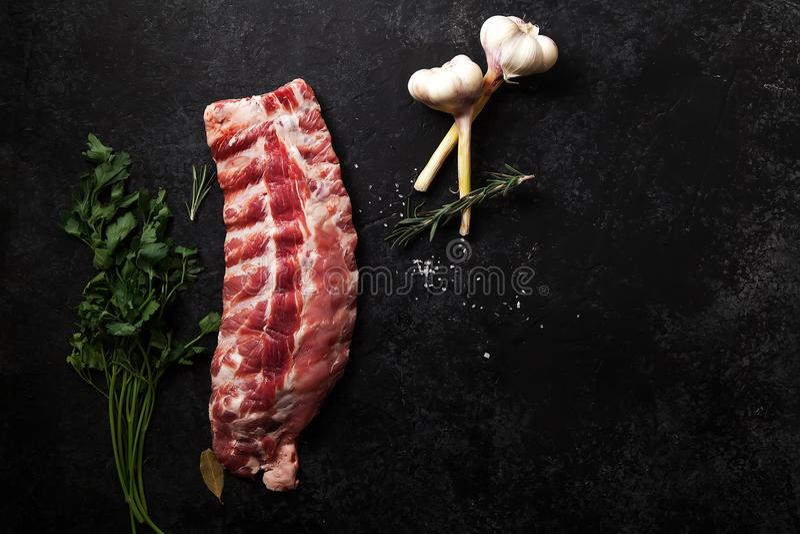 Costole di carne di maiale crude su fondo strutturato scuro immagini stock