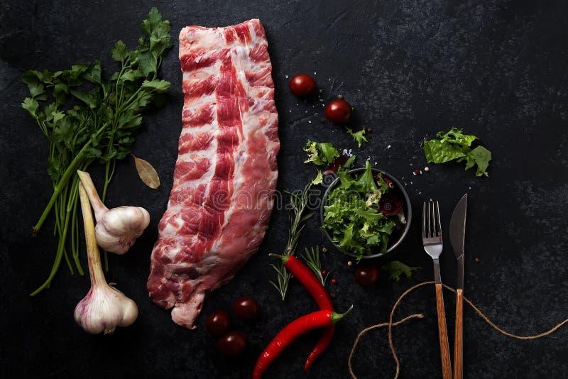 Costole di carne di maiale crude su fondo strutturato scuro immagini stock libere da diritti