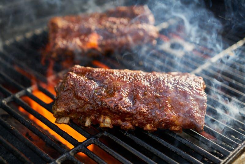 Costole di carne di maiale del Bbq che cucinano sulla griglia fiammeggiare fotografia stock