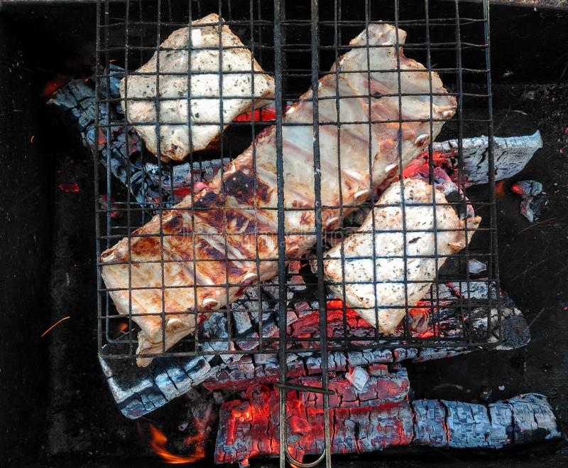 Costole di carne di maiale sulla griglia che cucina i carboni immagini stock