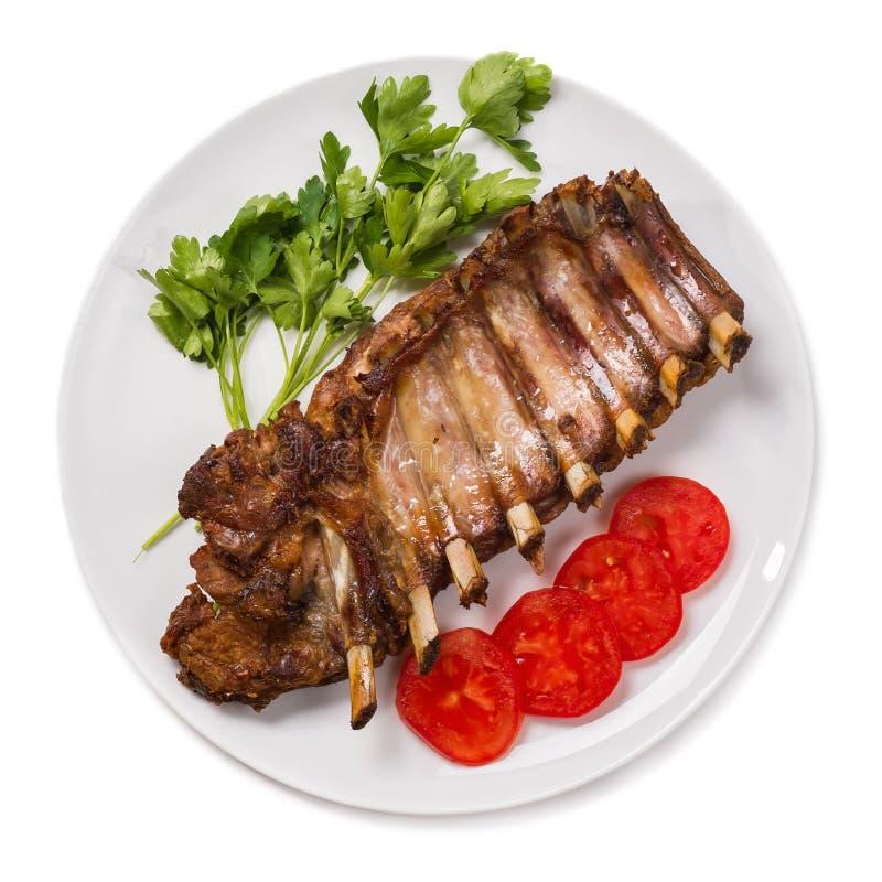 Costole di maiale arrostite col barbecue della carne di maiale su un fondo bianco fotografia stock