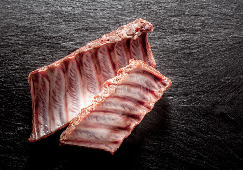 Costole di maiale crude su Grey Background strutturato immagini stock libere da diritti