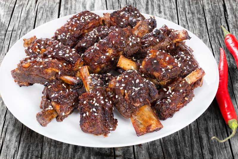 Costole di maiale piccanti cinesi sul piatto bianco spruzzato con sesamo fotografia stock libera da diritti