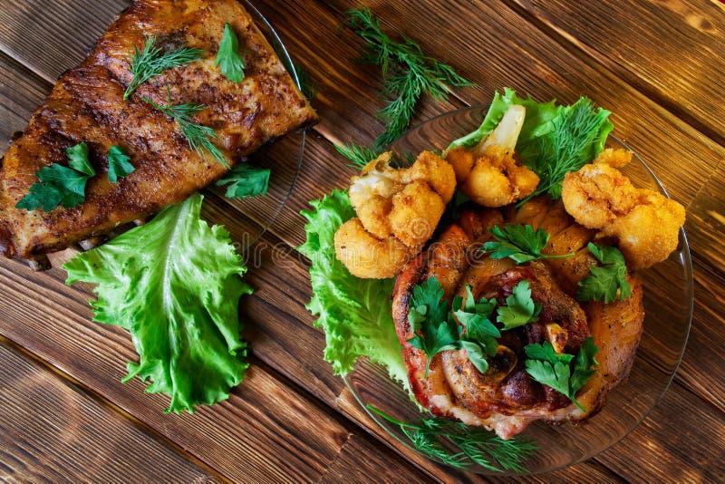Costole ed articolazioni di carne di maiale arrostite deliziose, condite con prezzemolo, lattuga, il cavolfiore e l'aneto La carn fotografia stock libera da diritti