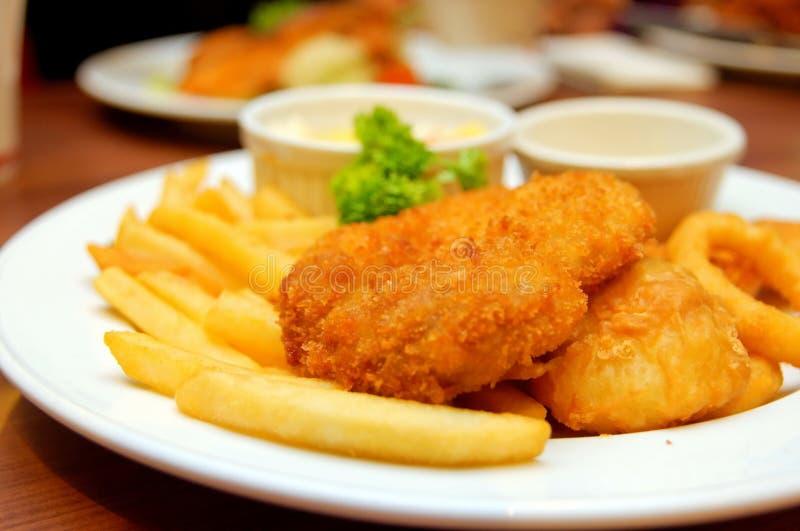 A costoleta da galinha e dos peixes seriu em um restaurante fotografia de stock