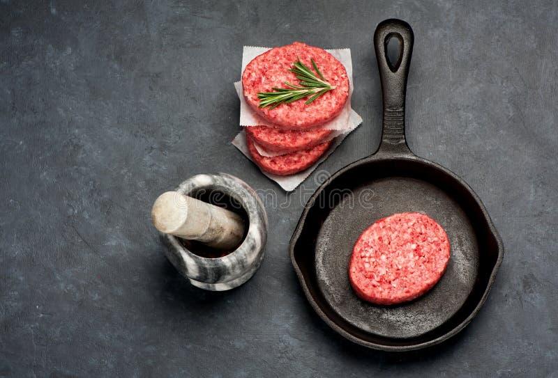 Costoletas cruas dos hamburgueres de uma carne de mármore em uma frigideira fotos de stock