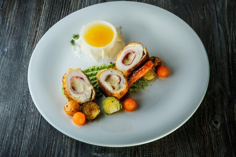 Costoletas dissecadas deliciosas de Kiev de galinha com vegetais e molho grelhados fotos de stock royalty free