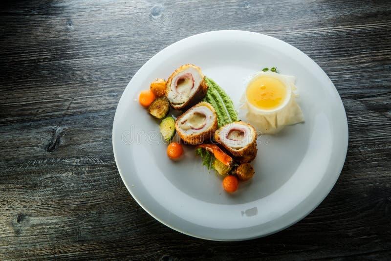 Costoletas dissecadas deliciosas de Kiev de galinha com vegetais e molho grelhados foto de stock