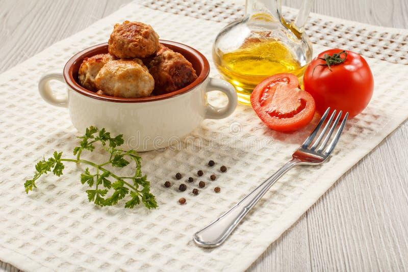 Costoletas fritadas na bacia de sopa cerâmica, tomates vermelhos da carne, bot de vidro foto de stock royalty free
