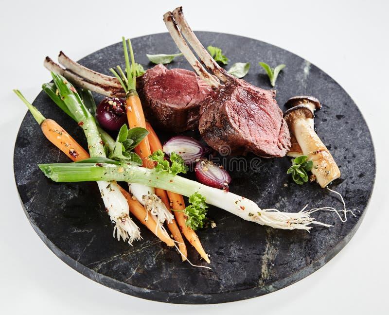 Costoletas raras médias do cordeiro com vegetais da mola imagem de stock royalty free