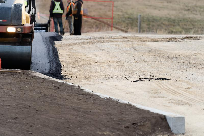 Costruction pracownicy kłaść nowego asfalt Dla Nowego parking zdjęcie royalty free