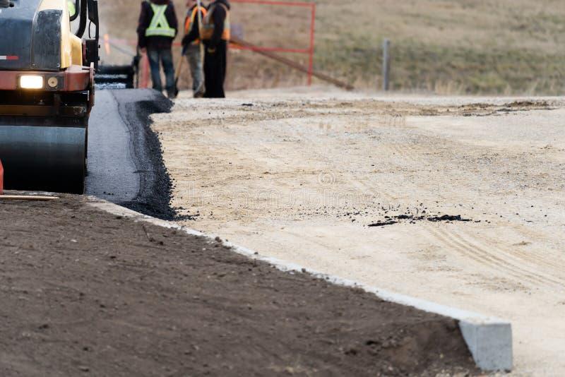 Costructions-Arbeitskräfte, die neuen Asphalt für neuen Parkplatz legen lizenzfreies stockfoto