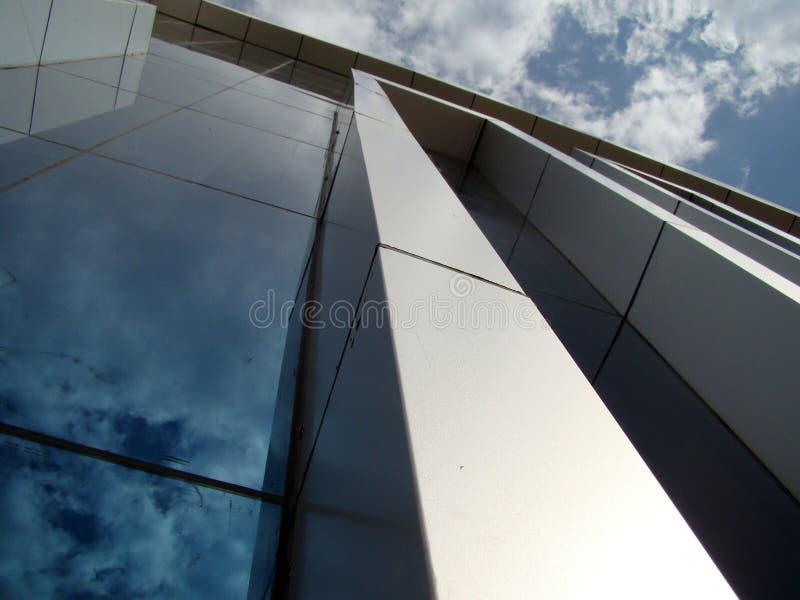 Costruendo su un fondo di cielo blu e delle nuvole con la riflessione in vetri immagine stock libera da diritti