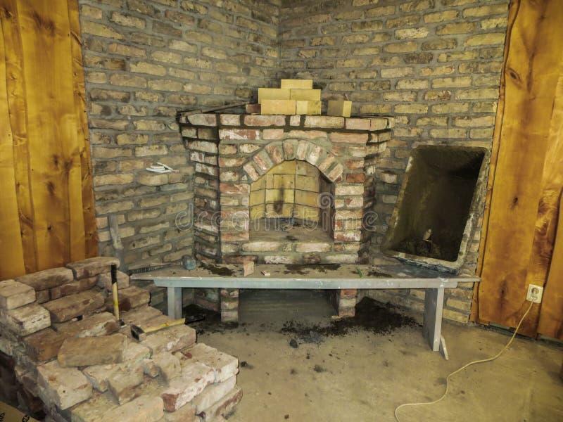 Costruendo un camino in una casa facendo uso di vecchi mattoni Bello lavoro di muratura immagine stock libera da diritti