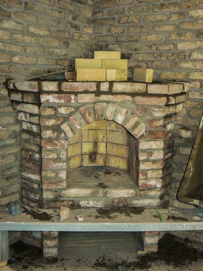 Costruendo un camino in una casa facendo uso di vecchi mattoni Bello lavoro di muratura fotografie stock