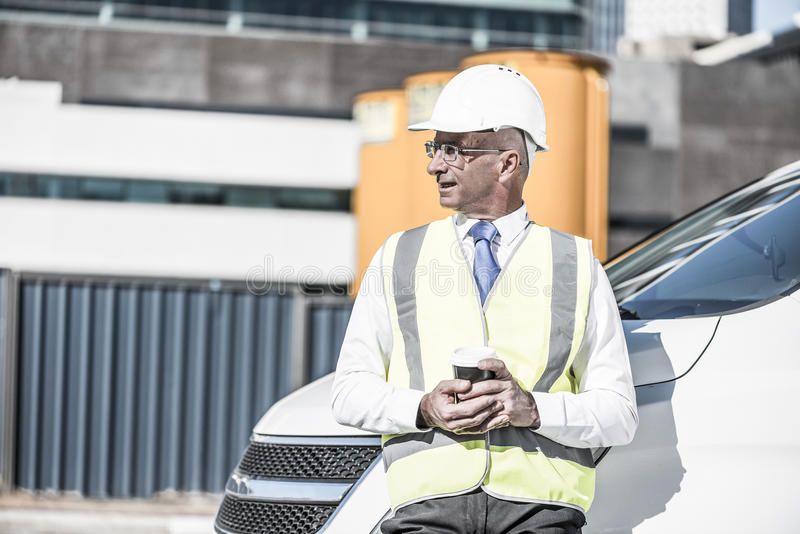 Costruisca il costruttore sul cantiere al giorno soleggiato con caffè i immagini stock libere da diritti
