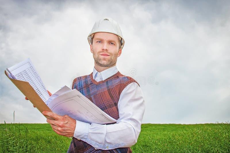 Costruisca l'architetto del costruttore con la documentazione del progetto in mani in casco bianco fotografie stock libere da diritti