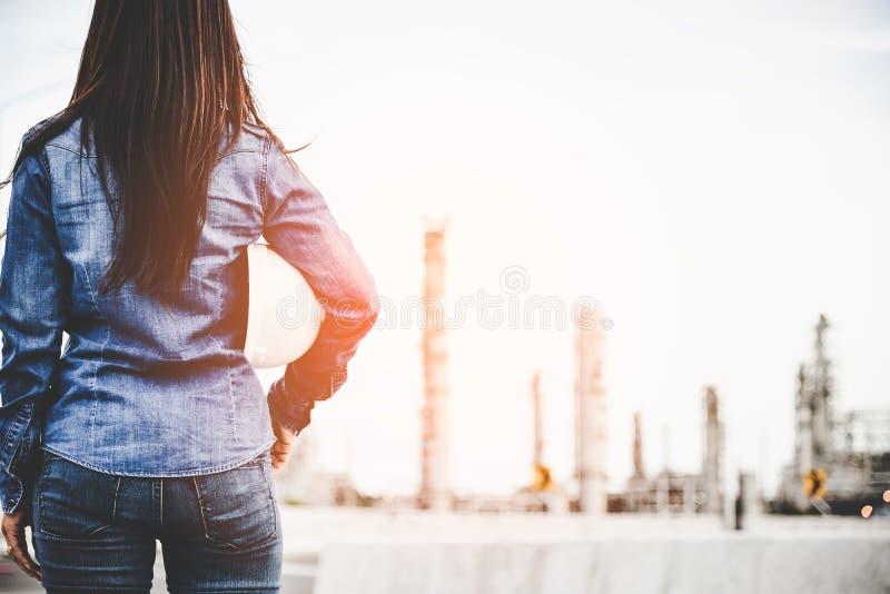 Costruisca la donna che tiene il casco bianco per il controllo di sicurezza dei lavoratori all'industria energetica della central fotografie stock libere da diritti