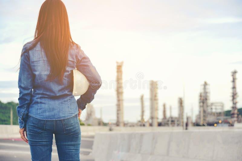 Costruisca la donna che tiene il casco ed il modello bianchi con la radio per il controllo di sicurezza dei lavoratori all'indust fotografie stock