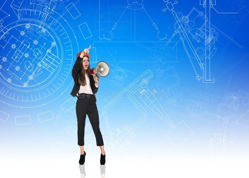 Costruttore arrabbiato della donna con il casco ed il megafono fotografia stock