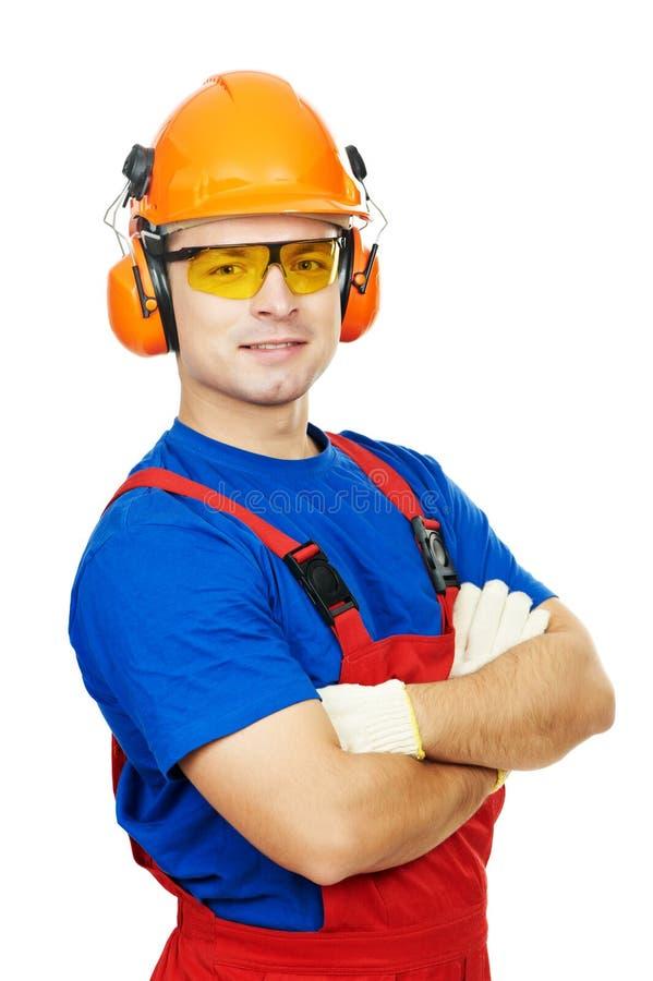 Costruttore in cappello duro, in paraorecchie ed in occhiali di protezione fotografia stock libera da diritti