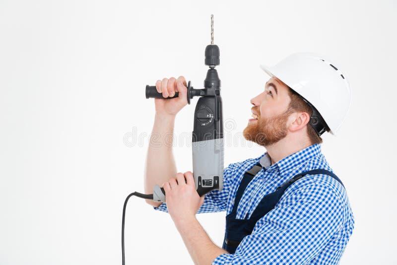 Costruttore in casco facendo uso del trapano e del cercare fotografia stock libera da diritti
