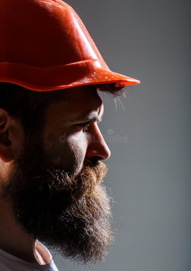 Costruttore in casco, martello, tuttofare, costruttori in elmetto protettivo Lavoratore barbuto dell'uomo con la barba, casco del immagini stock