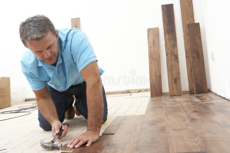 Costruttore che pone pavimentazione di legno fotografia stock libera da diritti