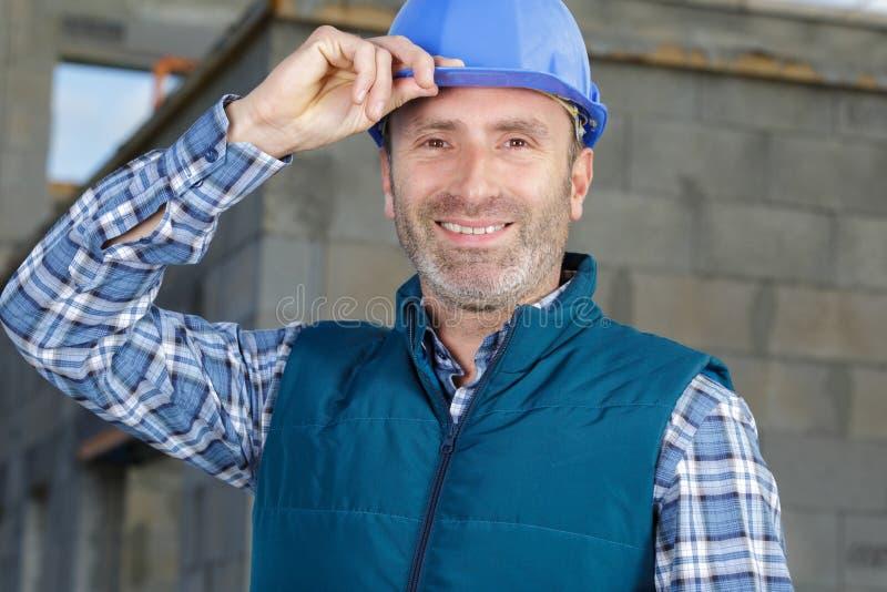 Costruttore dell'uomo nei sorrisi del casco fotografie stock