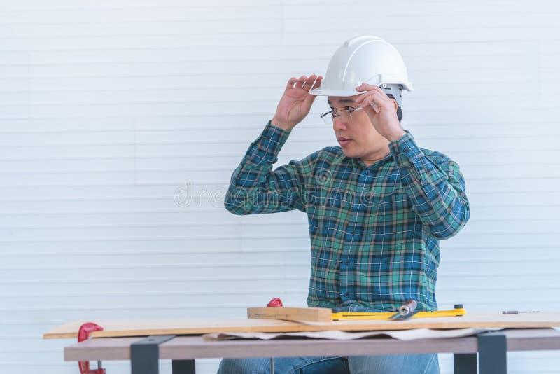 Costruttore della costruzione con gli strumenti e piano della carta sulla tavola di funzionamento fotografie stock libere da diritti