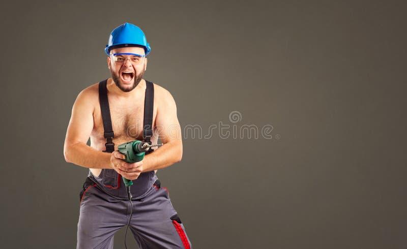 Costruttore divertente con un trapano dentro le sue mani fotografie stock