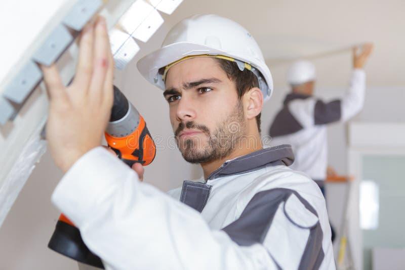 Costruttore in elmetto protettivo che perfora parete con il trapano all'interno immagine stock