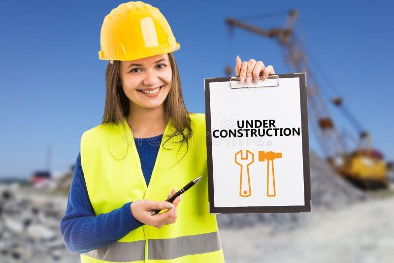 Costruttore femminile che presenta testo in costruzione sulla lavagna per appunti immagini stock libere da diritti