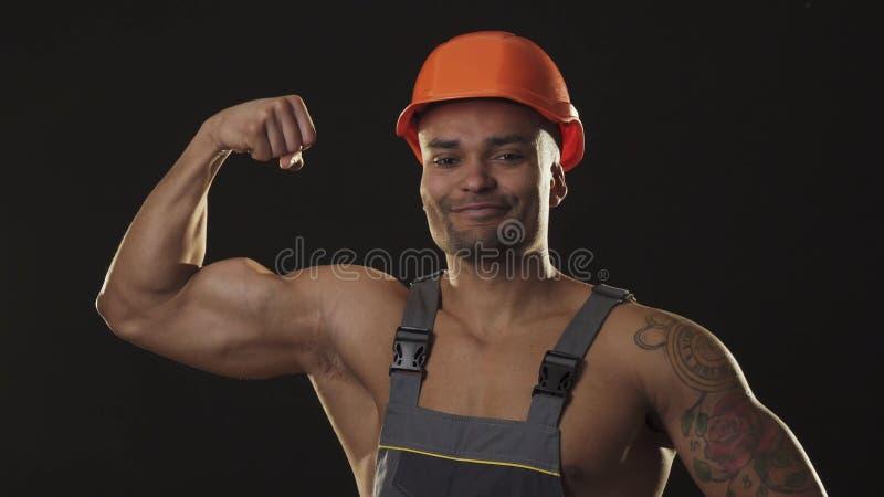 Costruttore maschio africano sexy strappato muscolare in abiti da lavoro ed elmetto protettivo che flette i muscoli fotografia stock