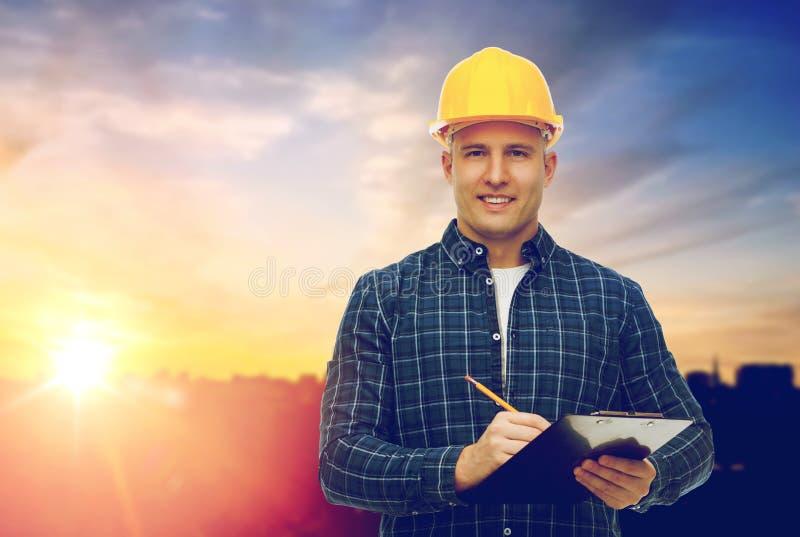 Costruttore maschio in casco giallo con la lavagna per appunti fotografia stock libera da diritti