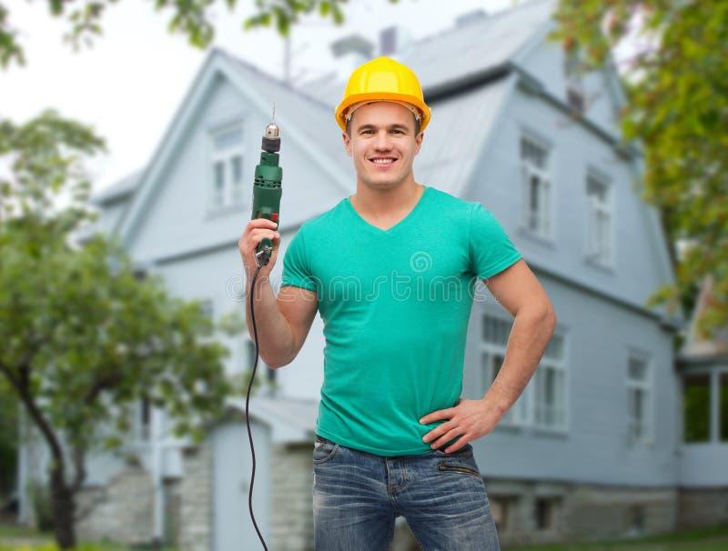 Costruttore maschio felice in casco con il trapano elettrico fotografia stock libera da diritti