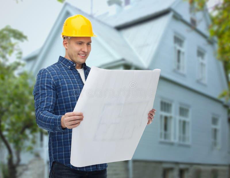 Costruttore sorridente con il modello sopra la casa fotografia stock