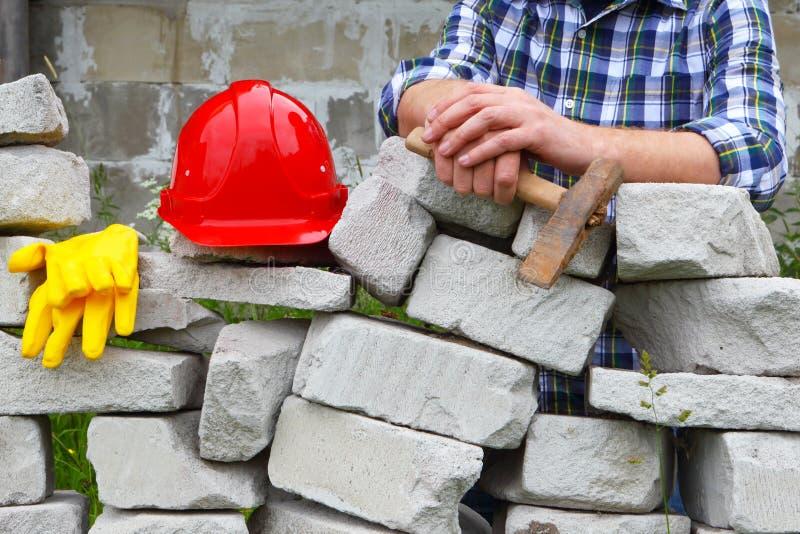 Costruttore in una camicia di plaid Casco e lavoro in pietra fotografie stock libere da diritti