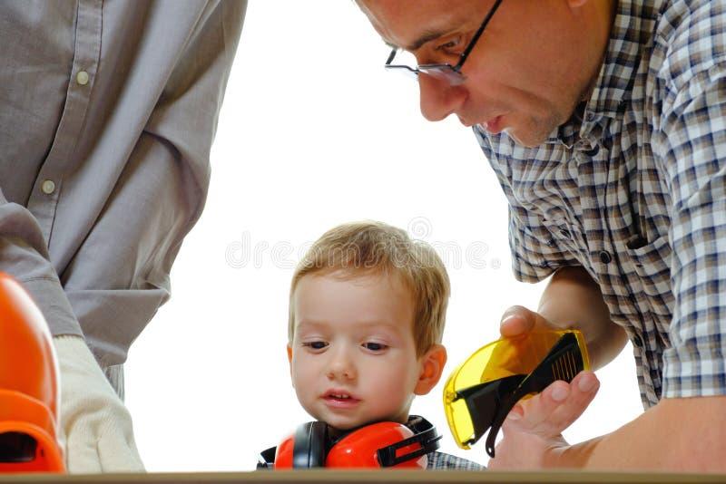 Costruttori che discutono con il bambino sopra il concetto del disegno Attrezzatura protettiva del casco su bianco immagine stock libera da diritti
