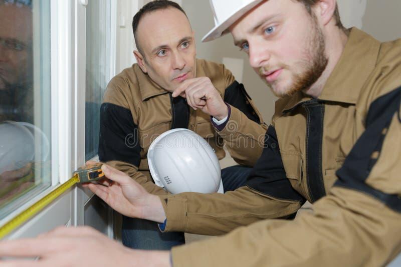 Costruttori che installano le finestre di misurazione fotografie stock