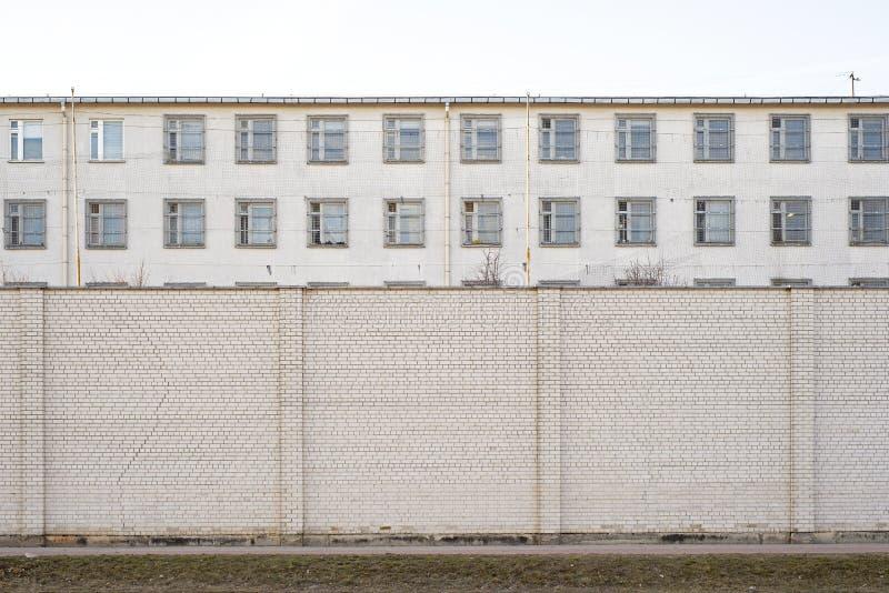Costruzione abbandonata circondata dal grande muro di mattoni bianco immagine stock libera da diritti