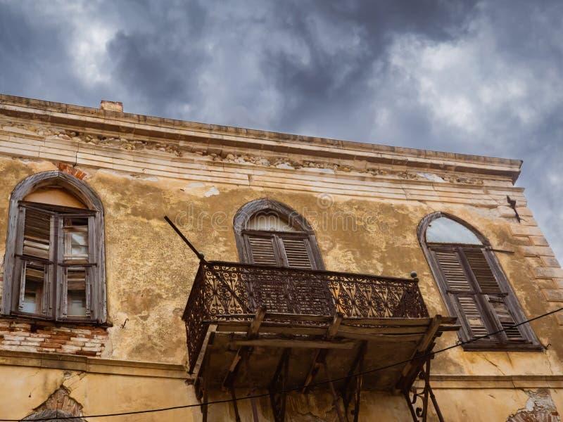 Costruzione abbandonata Mediterranea molto vecchia con il bello balcone e le finestre di legno - bellezza rustica immagine stock