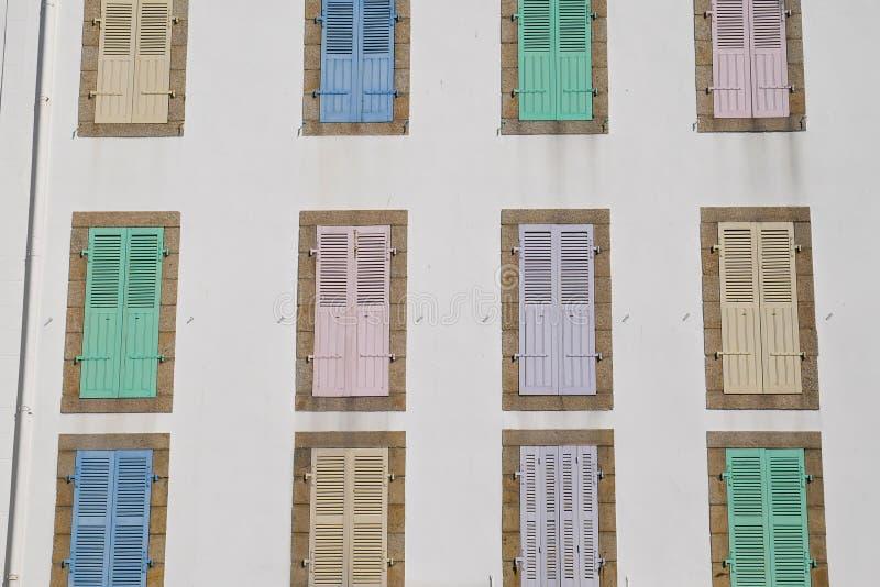 Costruzione bianca tipica dell'hotel con gli otturatori multicolori adorabili in Quiberon, hotel chiuso fuori stagione immagine stock libera da diritti